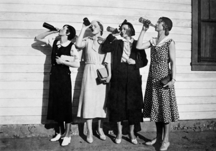 Flapper women drink in unison, ca. 1925.
